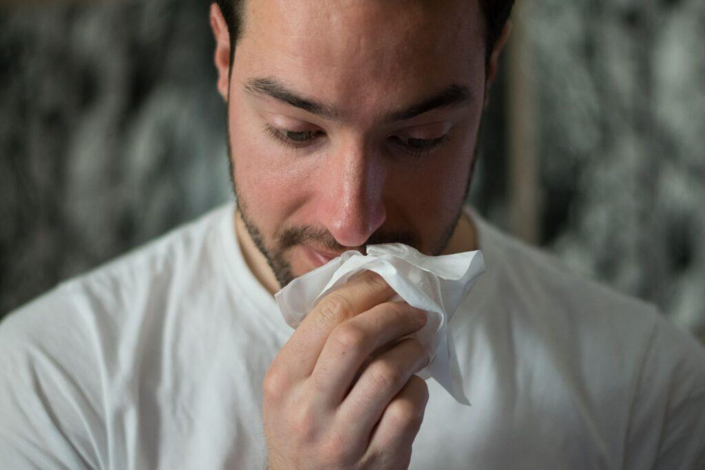 Homem gripado com lenço de papel na mão.