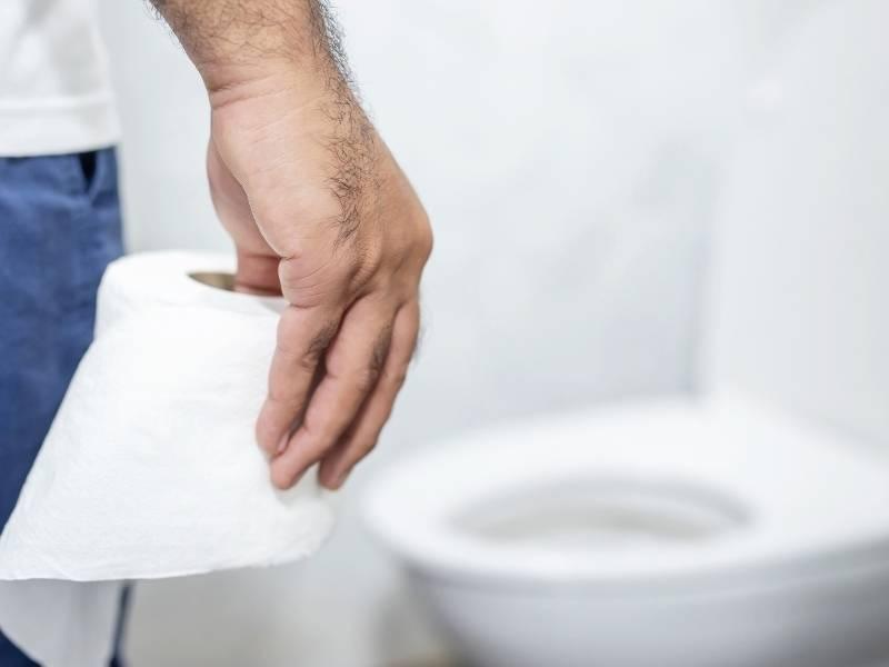 Homem no banheiro segurando um rolo de papel higiênico.