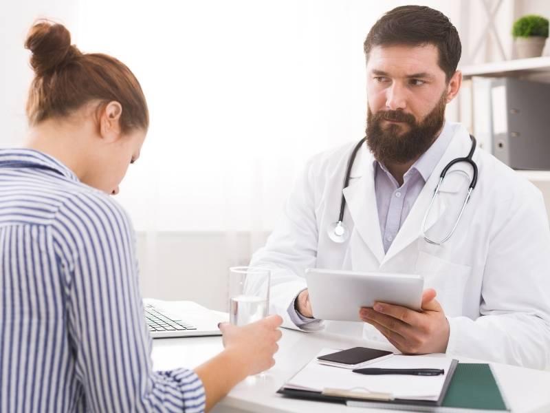Homem médico falando com paciente com copo de agua na mão.