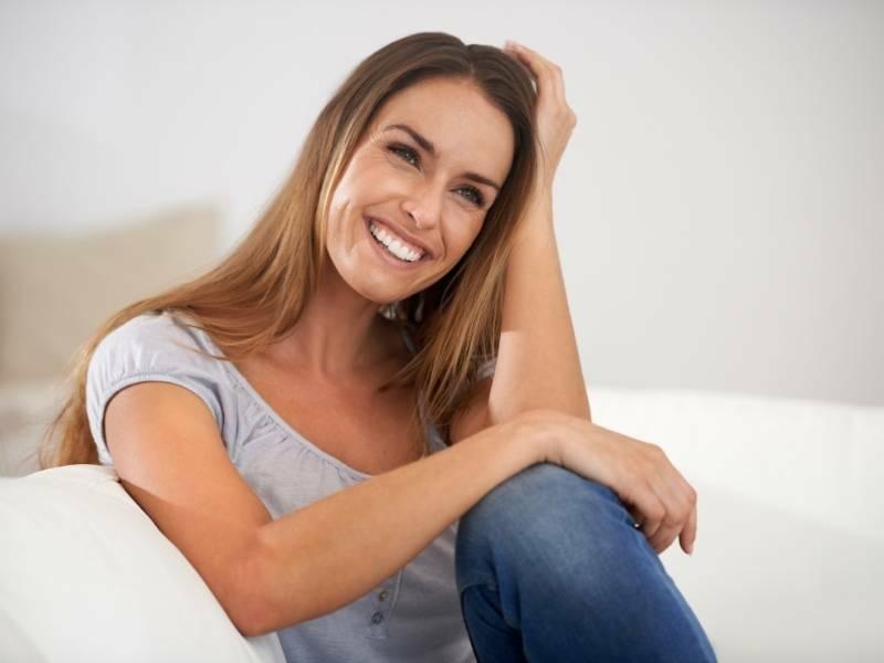 Mulher jovem sorrindo e sentada.