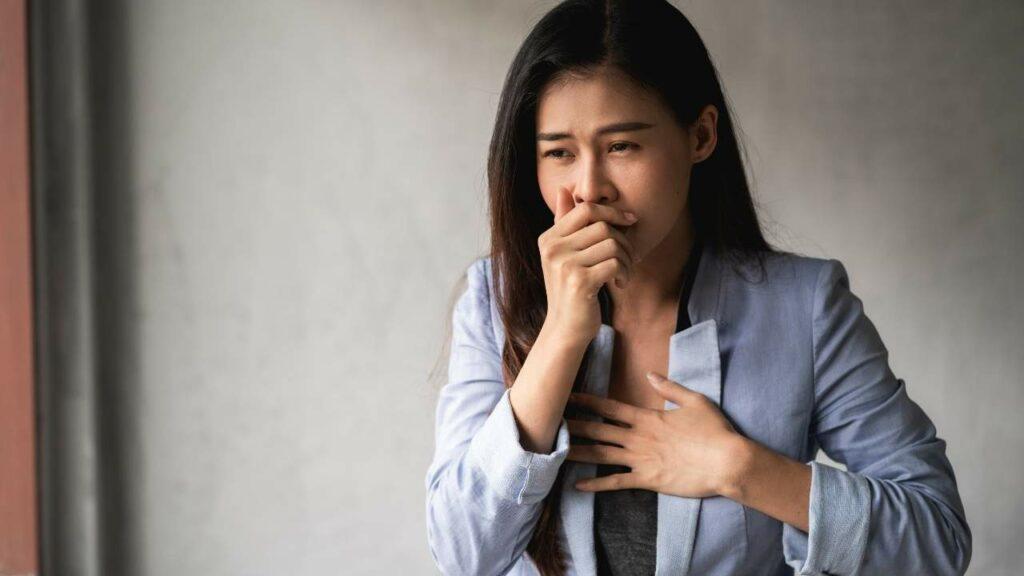Mulher jovem com dificuldade para respirar devido a crise de asma.
