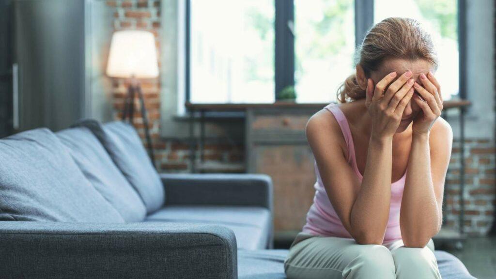 Mulher jovem sentada sendo afetada pelos sintomas da depressão.