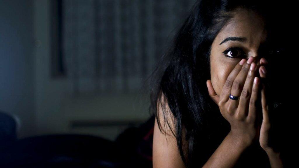 Mulher jovem com a mão na boca durante crise de pânico.