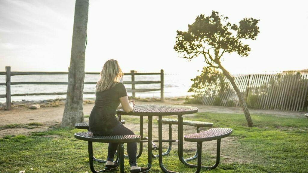 Mulher sentada sozinha em uma mesa ao ar livre.