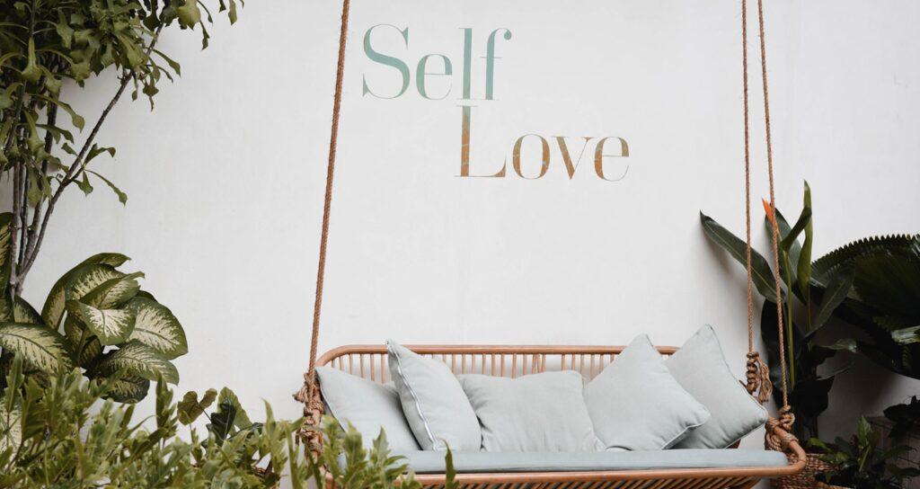 jardim com as palavras self love, ou autocompaixão, escritas na parede