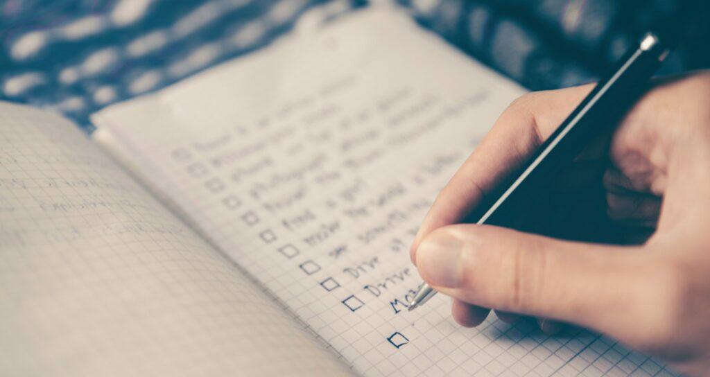 pessoa organizando sua rotina ao escrever suas atividades em um caderno