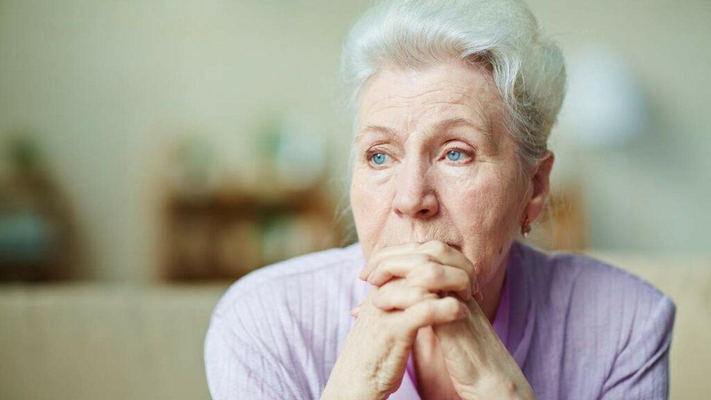 Mulher idosa com feição triste.