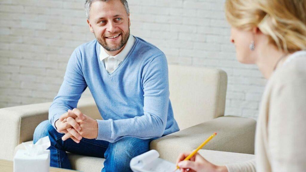Paciente homem sorrindo para psiquiatra.