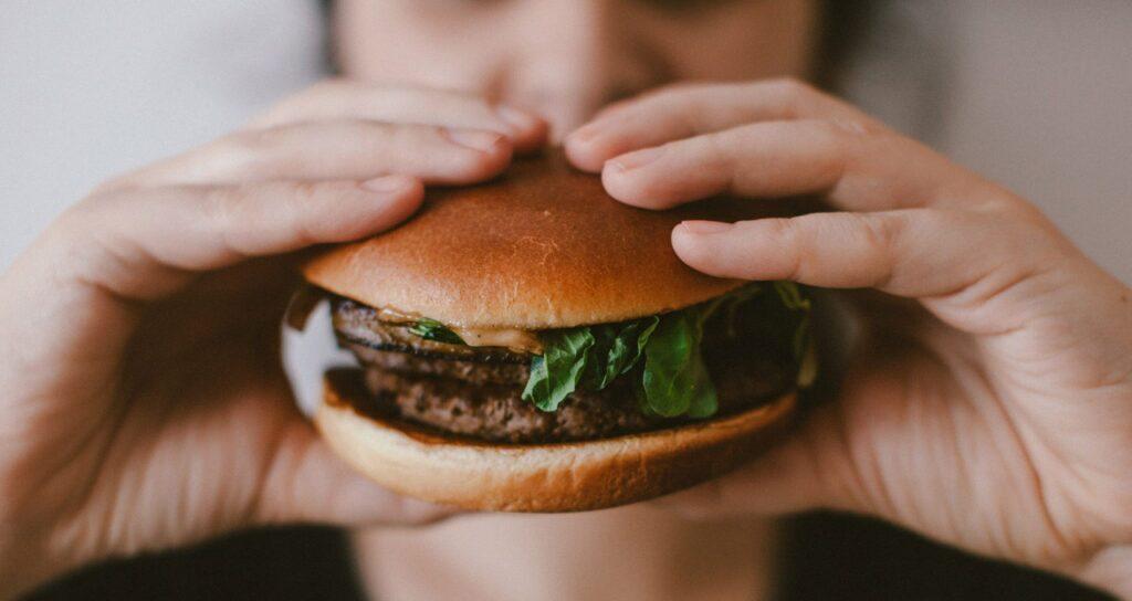 pessoa comendo hambúrguer vigorosamente, o que pode ser sinal de ansiedade