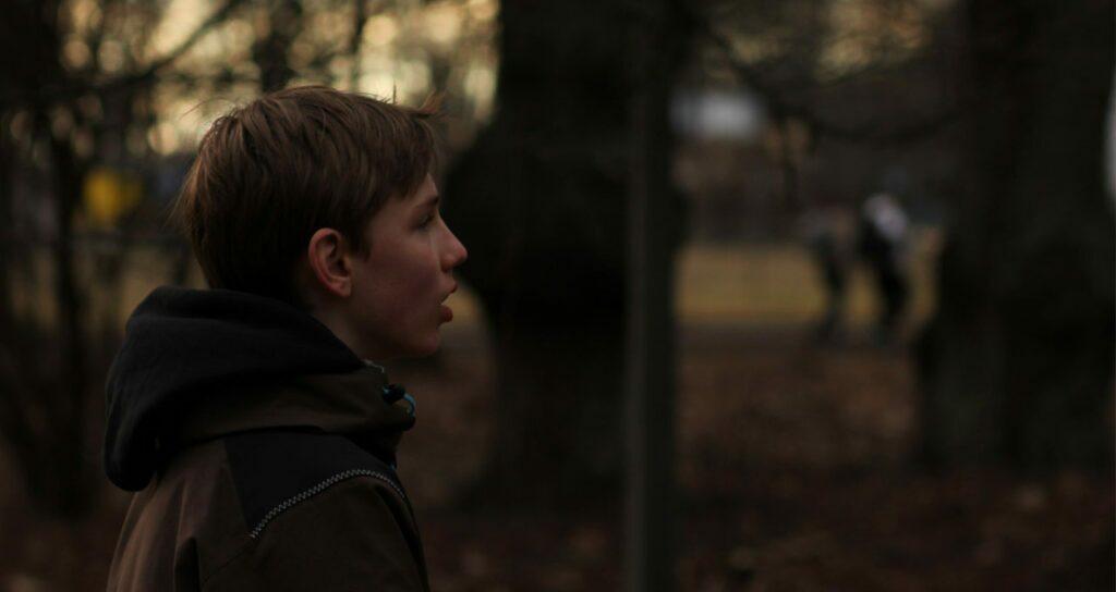 menino olhando para o horizonte com falta de ar, um dos sintomas da ansiedade