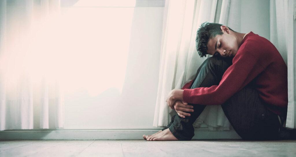 homem sentado no chão triste, demonstrando esgotamento mental