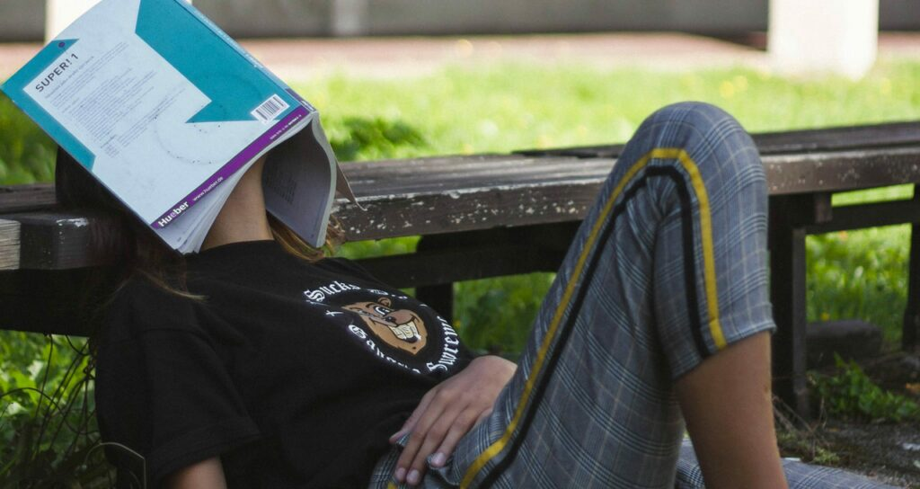 menina estudante com livro no rosto sinalizando exaustão, sintoma da ansiedade