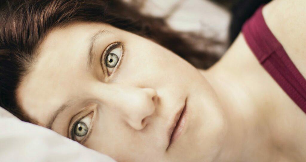 mulher deitada na cama com os olhos abertos, demonstrando sua insônia