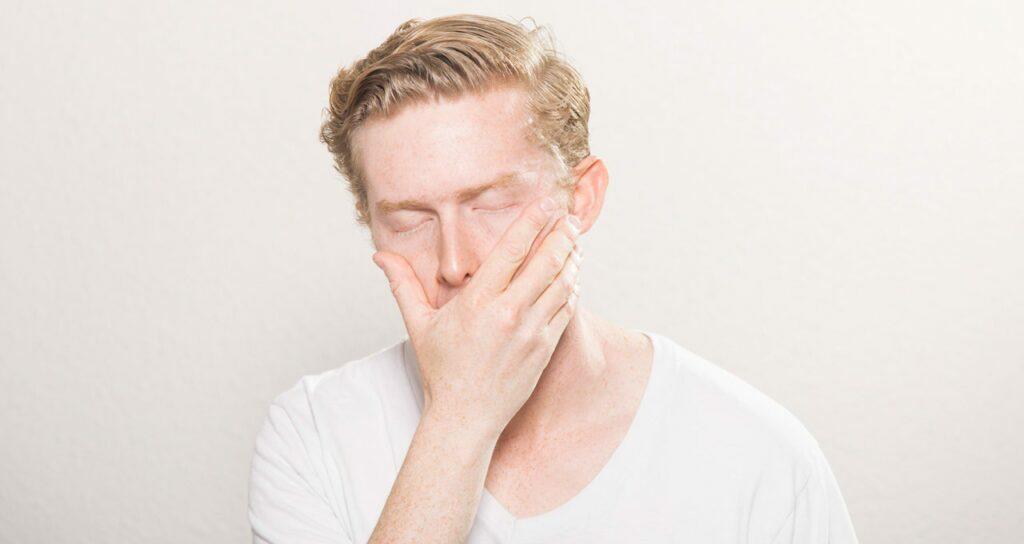 homem com a mão na boca por conta de náuseas e enjoo