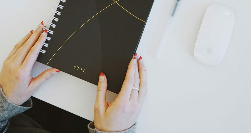 mulher ajeitando um caderno na mesa branca, sinalizando perfeccionismo