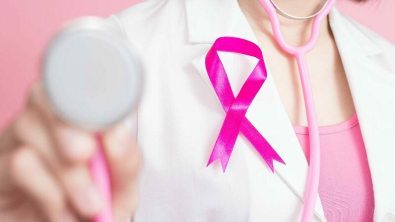 Médica com símbolo do outubro rosa alertando sobre o tratamento do câncer de mama.