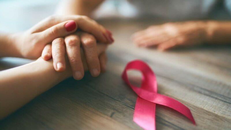 Duas pessoas com as mãos dados com o símbolo da prevenção do câncer de mama ao lado.