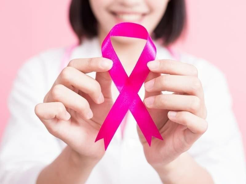 Mulher segurando laço símbolo do combate ao câncer de mama.