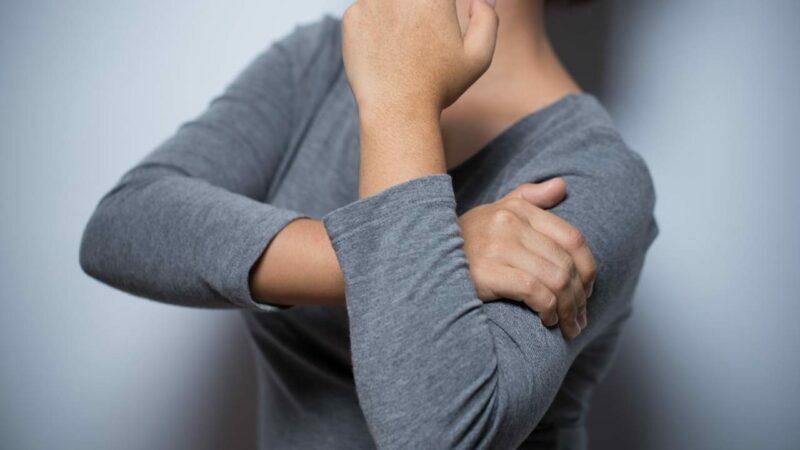 Mulher com dor no braço em razão de possível câncer de mama.