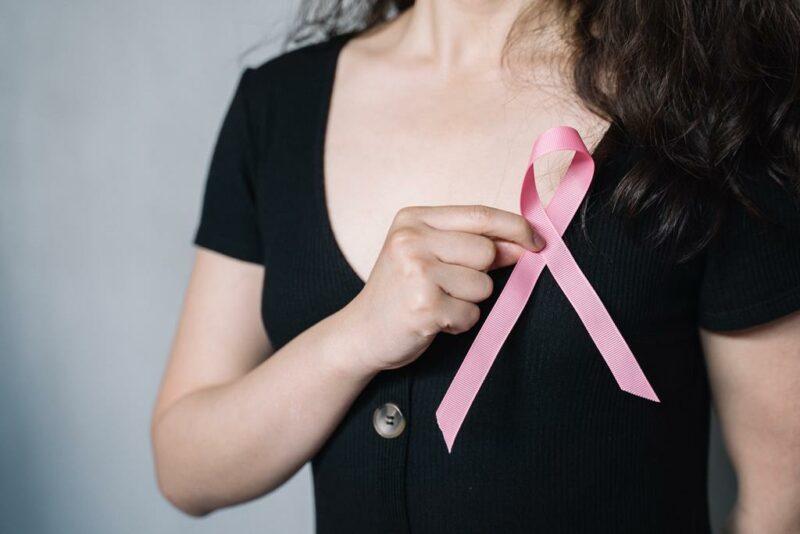 Mulher jovem segurando laço simbolo da campanha de combate ao câncer de mama.