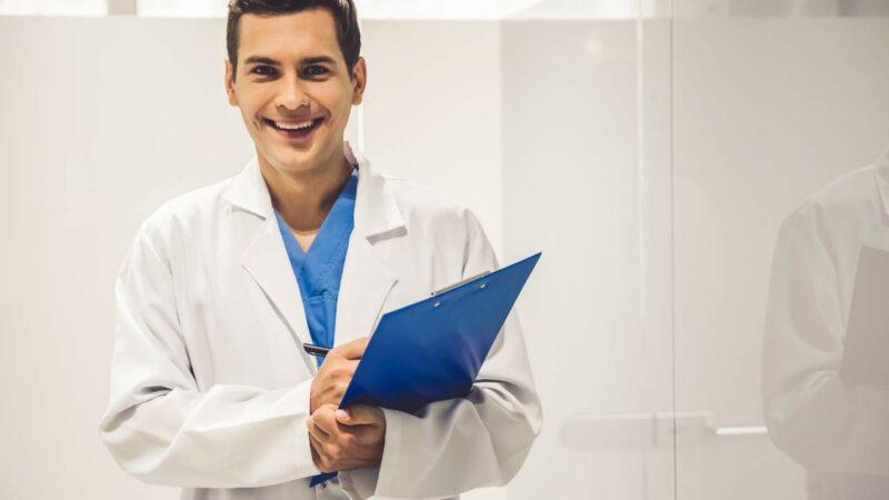 Médico mastologista homem segurando prancheta.