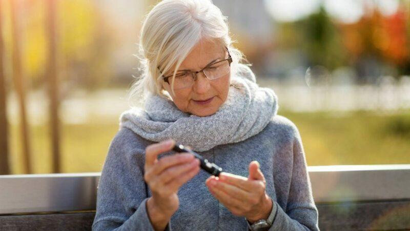 Mulher idosa aferindo diabetes.