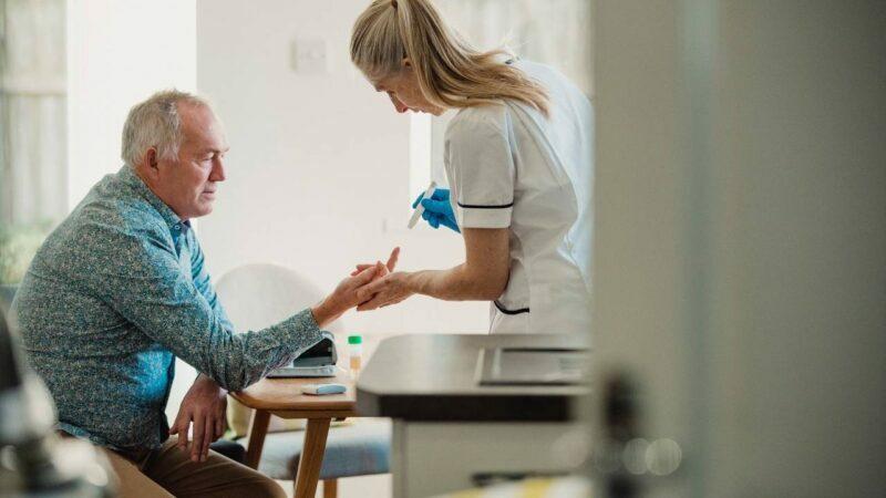 Enfermeira fazendo teste de diabetes tipo 1 e 2 em paciente.